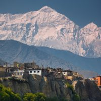 A small cliff town in front of the Himalayas in Nepal.