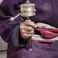 Old Tibetan woman holding buddhist prayer wheel.