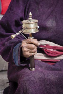 Old Tibetan woman holding buddhist prayer wheel.