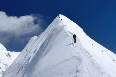 A mountain climber descends from a steep snowy peak